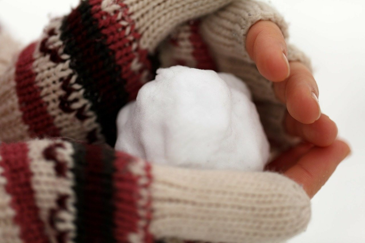 small snow ball in gloved hands