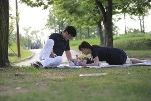 couple in the park with their baby