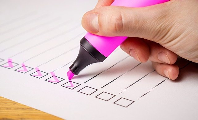 someone checking a checklist with a pink highlighter