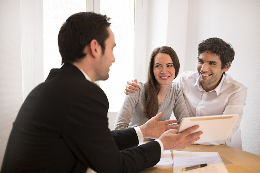 real estate agent speaking with happy couple