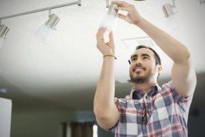 man wearing a plaid shirt fixing a light