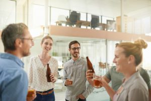 a group of young professionals talking while drinking beer