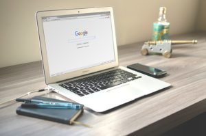 a lap top sitting on a desk displaying a google web search