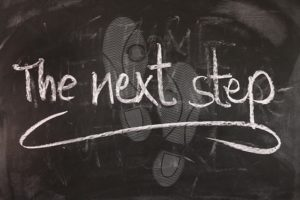 A chalkboard with footsteps and the words the next step.