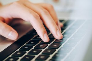 a close up of a hand typing on a silver laptop with black keys.