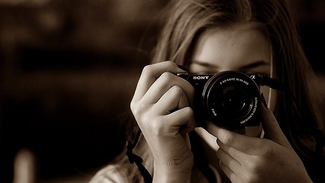 young woman taking a photo looking through the view finder.