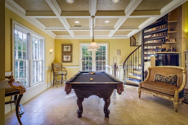 A nicely staged room in a house featuring a billiards table and a staircase.