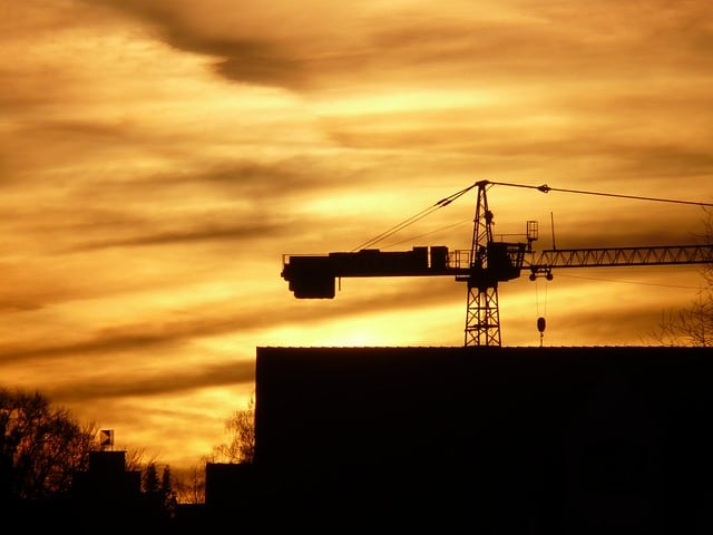 The silhouette of a construction crane against a yellow sunset.